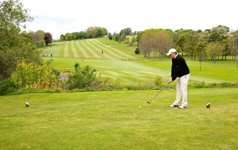 A man playing golf on an open field